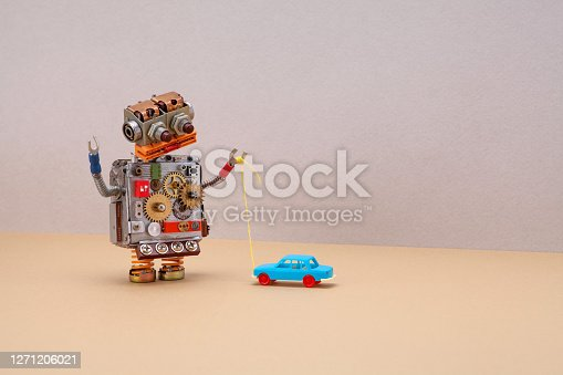 Robot plays with a vintage toy car. Gray beige background, copy space