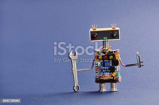istock Robot serviceman with hand wrench and screwdriver on blue background. Abstract mechanical toy worker made of electronic circuits, chip capacitors vintage resistors 656238582