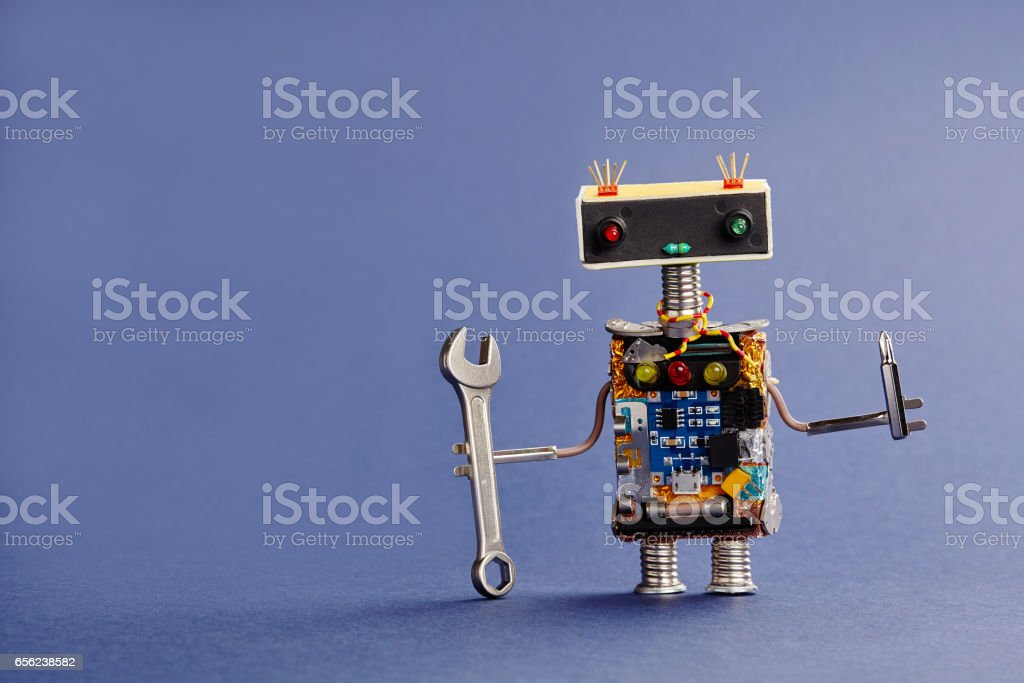 Robot serviceman with hand wrench and screwdriver on blue background. Abstract mechanical toy worker made of electronic circuits, chip capacitors vintage resistors stock photo
