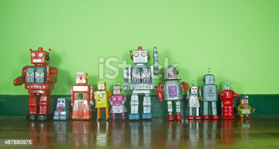 a line of retro robots on a wooden floor
