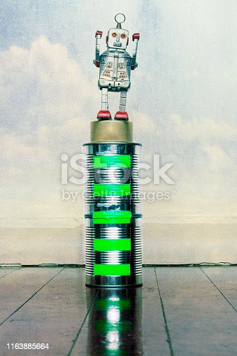 robot toy on top of a fully charged battary  made of old tin cans