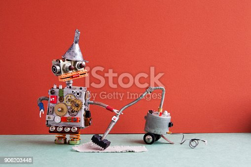 istock Robot vacuum cleaner machine service. Funny robotic toy metal funnel hopper, cogs wheels gears metallic body, cleaning carpet process, red wall room interior 906203448