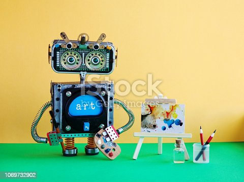 istock Robot with pencil brush and palette. Handwritten watercolor abstract picture wooden easel. Yellow wall green floor background. 1069732902