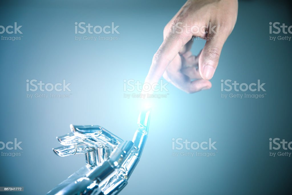 Robotic and human hands reaching to each other stock photo