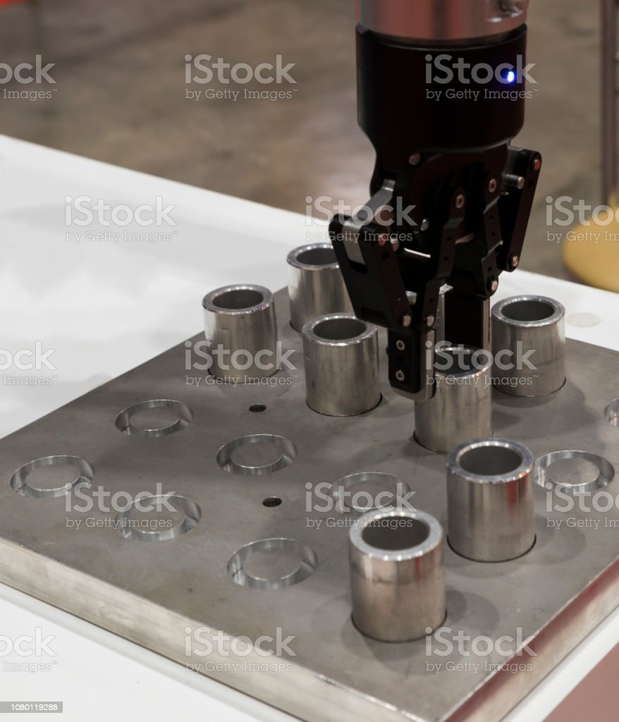 Robotic arm clamp sample and transfer in metal plate stock photo