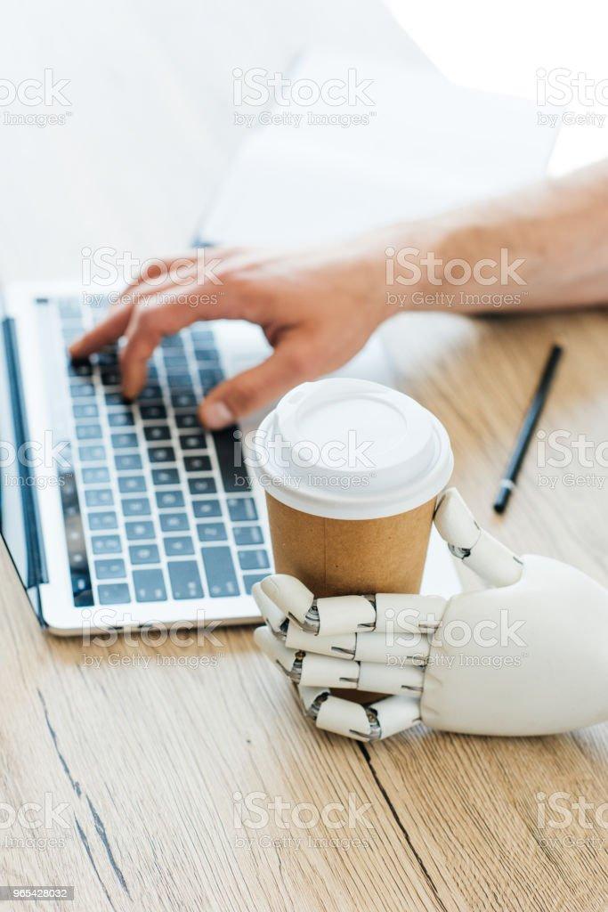 일회용 커피 컵과 나무 테이블에서 노트북을 사용 하 여 인간의 손을 들고 로봇 팔 - 로열티 프리 STEM-주제 스톡 사진