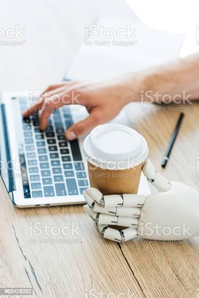 일회용 커피 컵과 나무 테이블에서 노트북을 사용 하 여 인간의 손을 들고 로봇 팔 STEM-주제에 대한 스톡 사진 및 기타 이미지