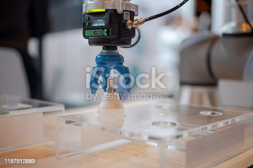 istock Robotic arm picking up light bulb 1157512683