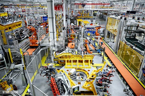 182463664 istock photo Robotic arms in a car manufacturing factory 916875596