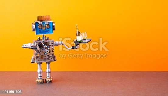 istock Robotic food delivery service concept. Laughing robot waiter holds tray with wine glasses, bottle of champagne. Autonomous steampunk mechanical toy on orange wall, brown floor background. copy space. 1211561506