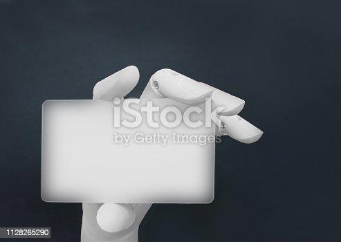 910163152 istock photo Robotic hand holding blank card 1128265290