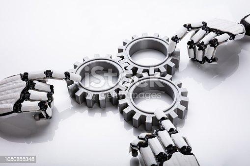 istock Robotic Hands Connecting Gears 1050855348