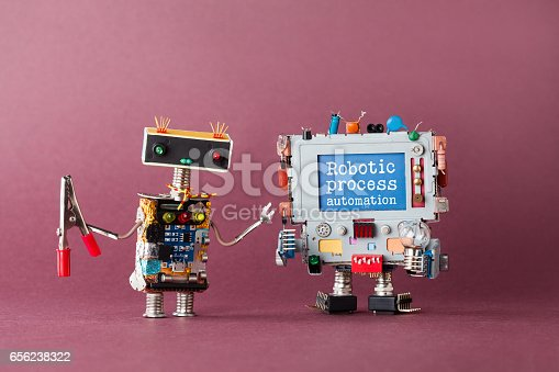 istock Robotic process automation industry 4.0 concept. IT specialist robot with pliers looking at colorful computer. New economic future message on blue display. Violet background, macro view 656238322
