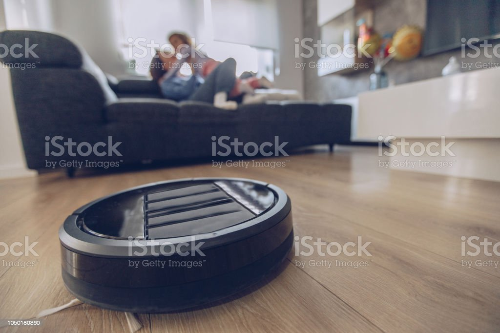 Robotic Vacuum Cleaner Cleaning Floor While Mother And