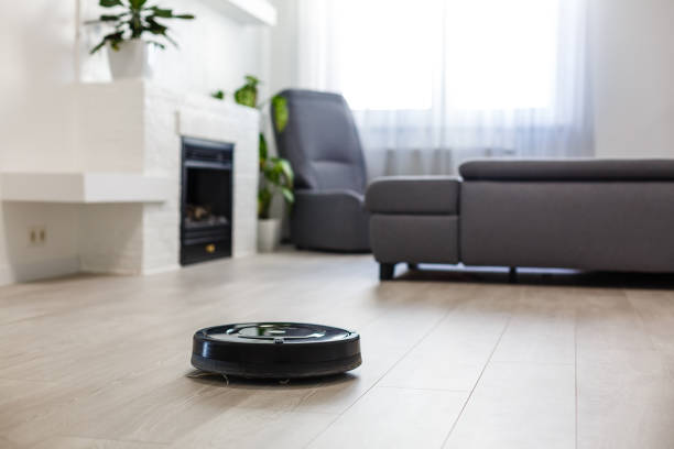 Robotic vacuum cleaner on laminate wood floor in living room stock photo