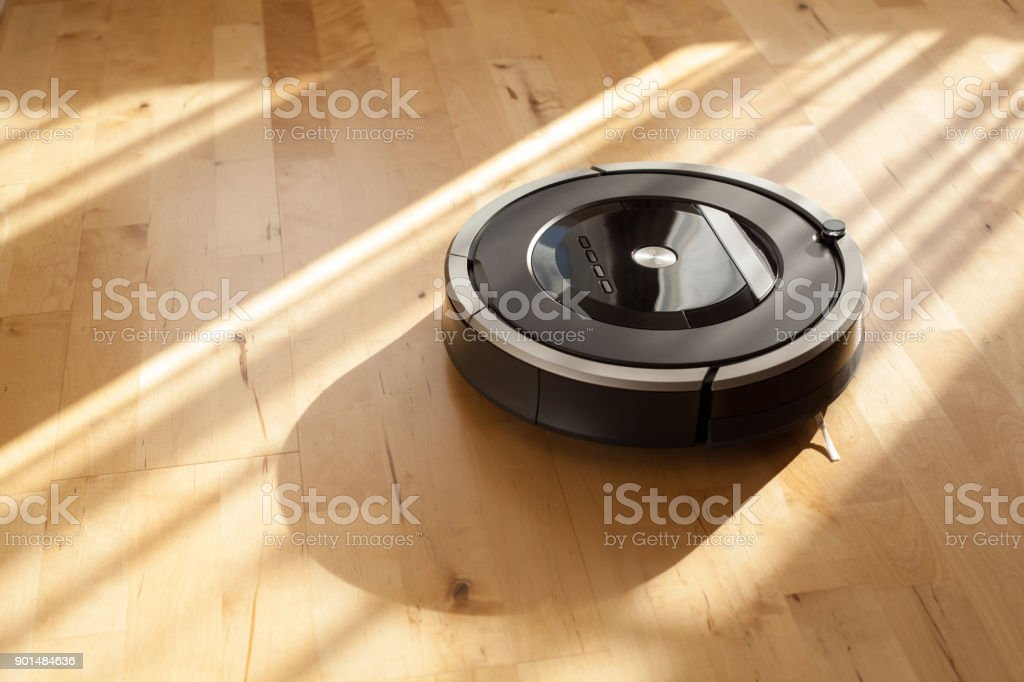 robotic vacuum cleaner on laminate wood floor smart cleaning technology stock photo