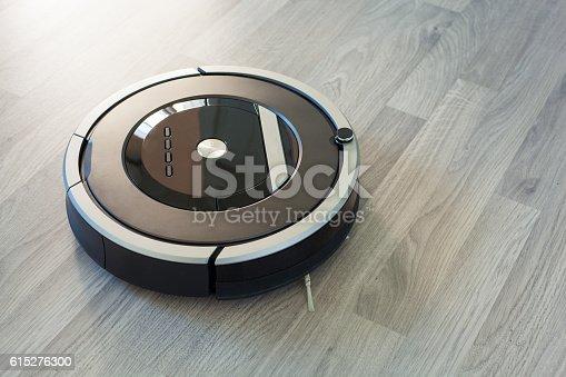 Fotografía de Robotic Vacuum Cleaner On Laminate Wood Floor Smart Cleaning Tec y más banco de imágenes de Aspiradora