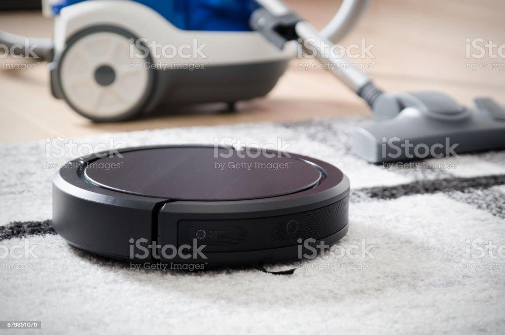 Robotic vacuum cleaner working on carpet stock photo