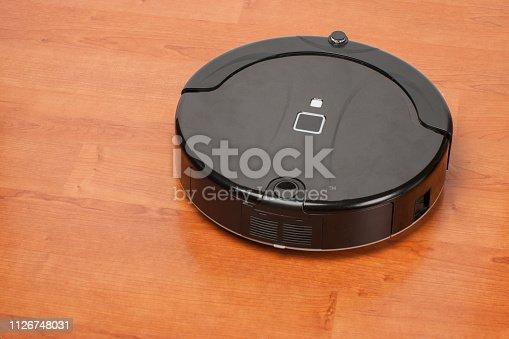 istock robotic vacuum cleaner working on laminate wood floor. smart cleaning technology housekeeping 1126748031