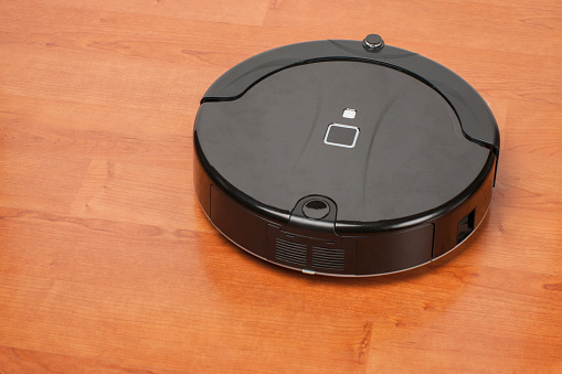 istock robotic vacuum cleaner working on laminate wood floor. smart cleaning technology housekeeping 1126748031
