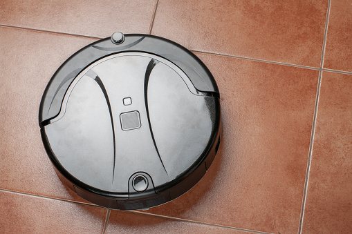 istock robotic vacuum cleaner working on tile floor. smart cleaning technology 1126748035