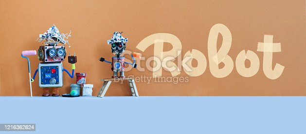 910163152 istock photo Robotics designers and artificial intelligence concept. Two painter artist robots decorated the wall in brown. The little robot painted the word Robot. 1216362624