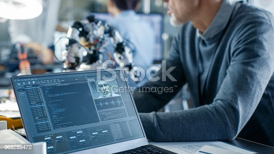 istock Robotics Engineer Manipulates Voice Controlled Robot, Laptop Screen Shows Speech and Face Recognition Software. In the Background Robotics Reseatch Center Laboratory. 968289472