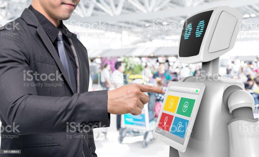Robotics Trends technology business concept. Man suit point finger to Autonomous personal assistant robot for navigation direction in airport blur background. 3D rendering stock photo