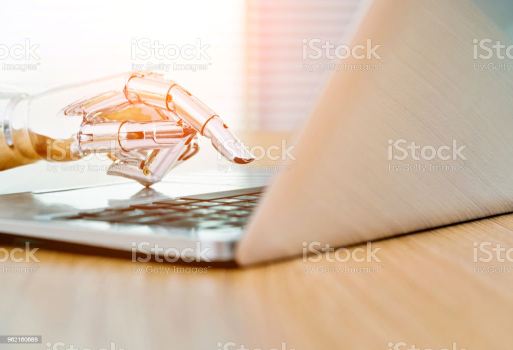 Robot's hand typing on keyboard stock photo
