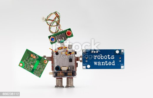 istock Robots wanted electronic wokers hiring concept. Toy robotic character handing circuit micro chip circuits on gray background 656238112
