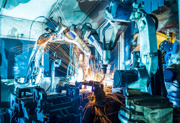 Robots welding in a car factory Welding robots movement in a car factory manufacturing stock pictures, royalty-free photos & images