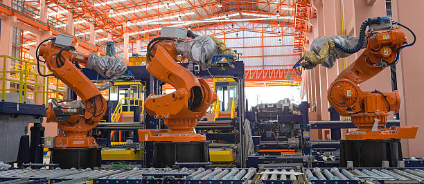 robots welding in a production line - robotics manufacturing stock photos and pictures
