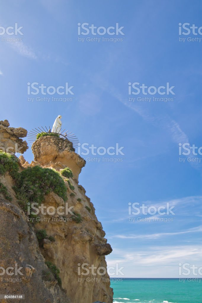 rocher de la vierge statue of virgin mary on top of high cliff on atlantic coastline in blue sky in Biarritz, Basque country, France stock photo
