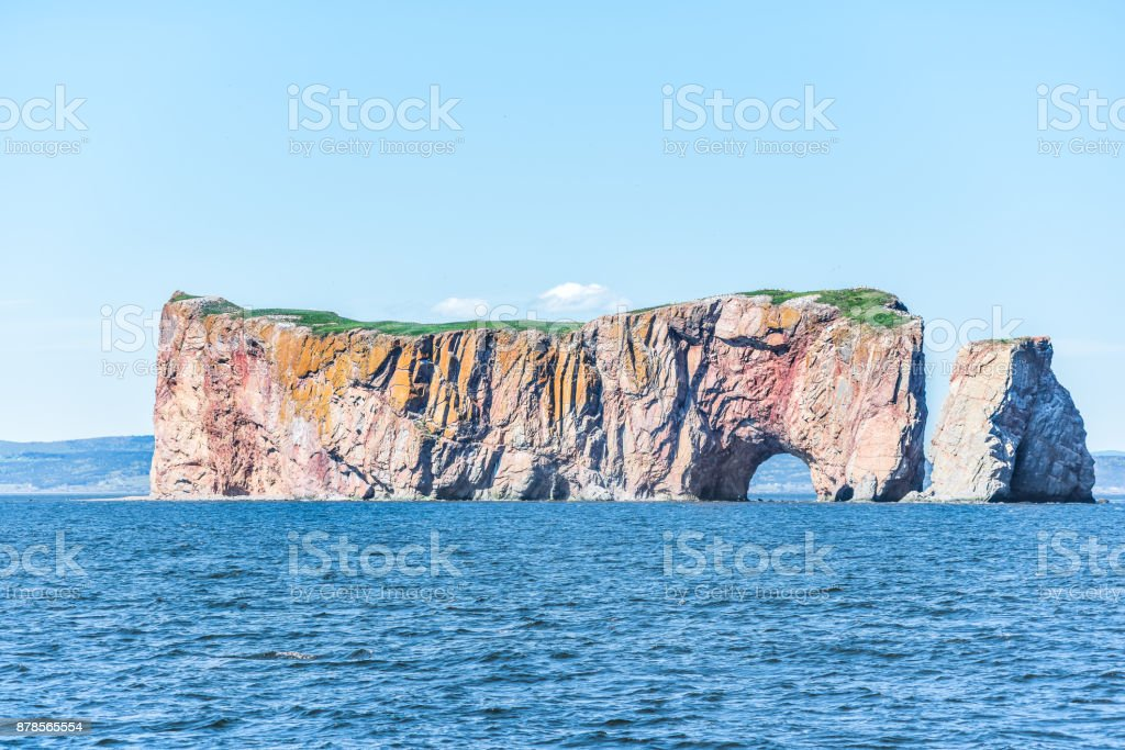 Rocher Perce rock in Gaspe Peninsula, Quebec, Gaspesie region closeup with blue water stock photo