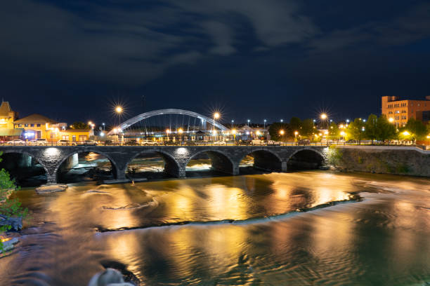 rochester new york along the genesee river at night - rochester ny skyline stock photos and pictures