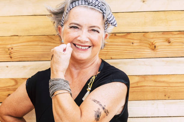 Rock and alternative cheerful senior caucasian woman show her tatoo on the arm smiilng at the camera - no limit age to have fun and enjoy lifestyle for old people - wooden background stock photo