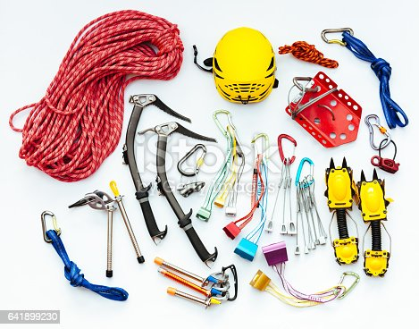 Rock and ice climbing equipment. It includes a pair of ice axes and crampons, a helmet, a red snow belay plate, a prussik loop, rock protection and ice screws.
