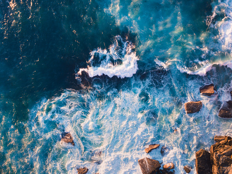 Aerial view of waves and some rocks.