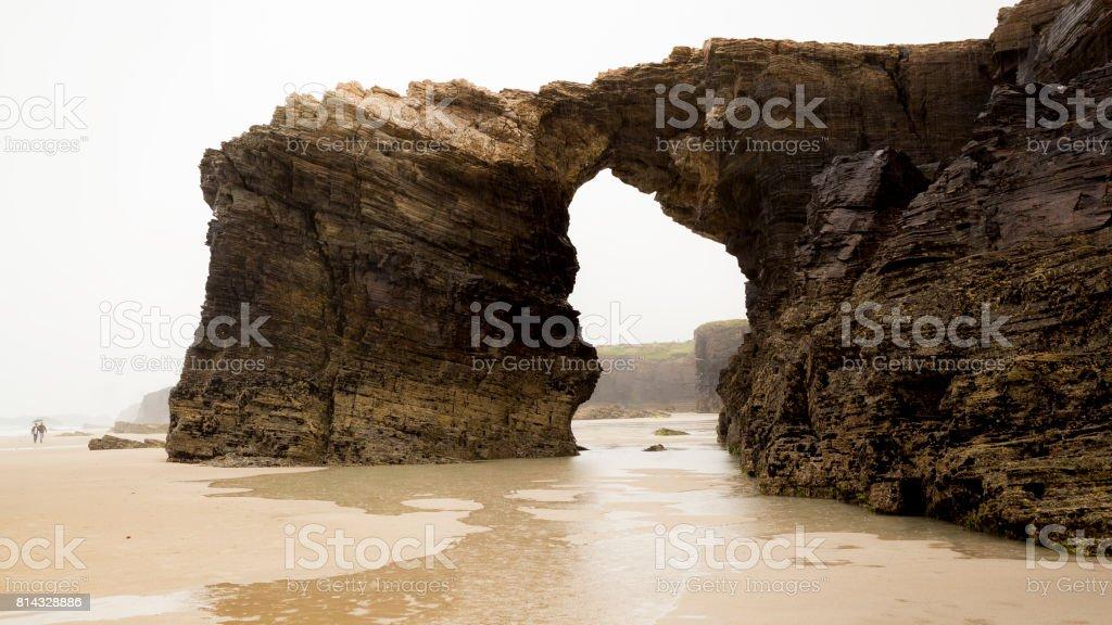 Rock arch in a beach stock photo