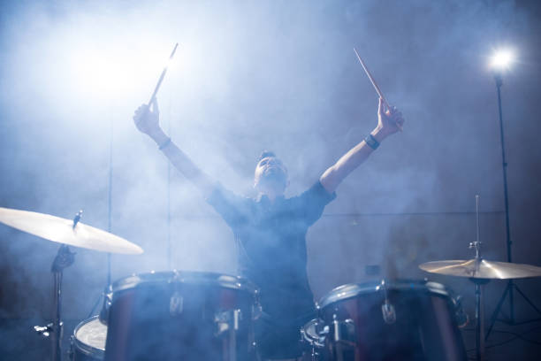 Rock band drummer on stage Rock band drummer raising his arms on stage with light and smoke drummer stock pictures, royalty-free photos & images