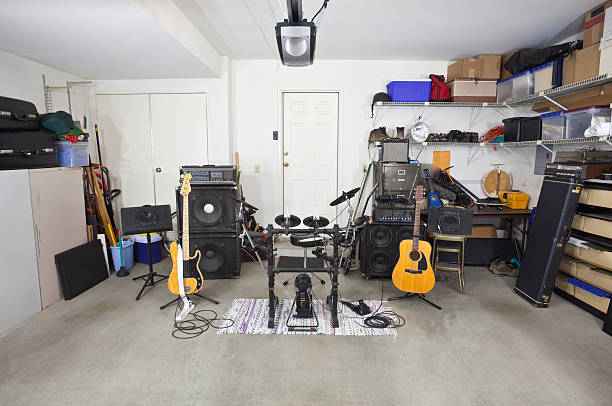 rock band music equipment in cluttered garage - performance group stock photos and pictures