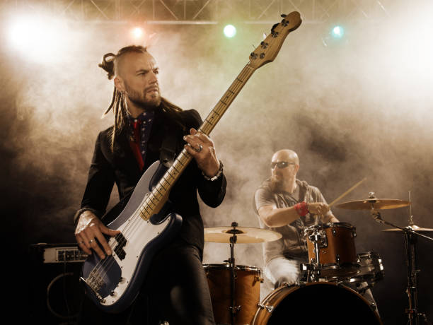 Rock band performs on stage. Bassist in the foreground. stock photo