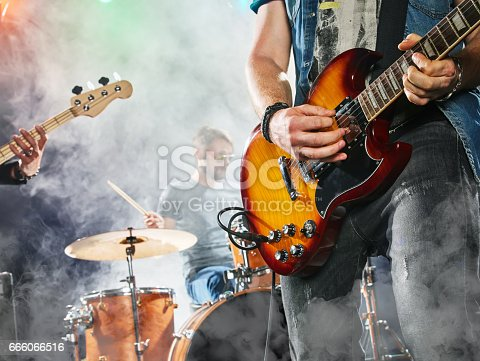 istock Rock band performs on stage. Guitarist, bass guitar and drums. 666066516