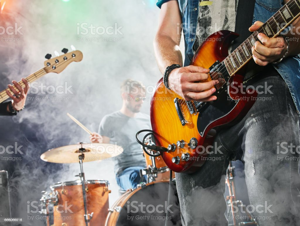 Rock band performs on stage. Guitarist, bass guitar and drums. stock photo