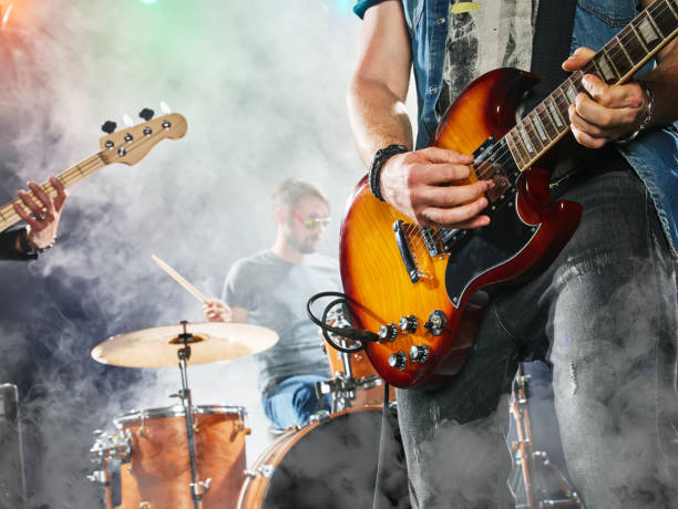 rock band performs on stage. guitarist, bass guitar and drums. - rock music stock pictures, royalty-free photos & images