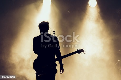 istock Rock band performs on stage. Guitarist plays solo. silhouette of guitar player in action on stage behind lights. 897638566