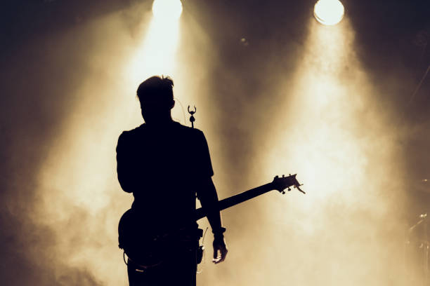 Rock band performs on stage. Guitarist plays solo. silhouette of guitar player in action on stage behind lights. Rock band performs on stage. Guitarist plays solo. silhouette of guitar player in action on stage in front of concert crowd. Smoke. Light guitarist stock pictures, royalty-free photos & images