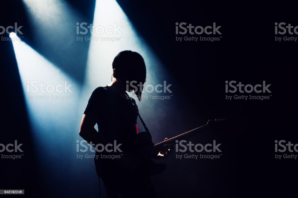 Rock band performs on stage. Guitarist plays solo. silhouette of guitar player in action on stage behind lights. stock photo