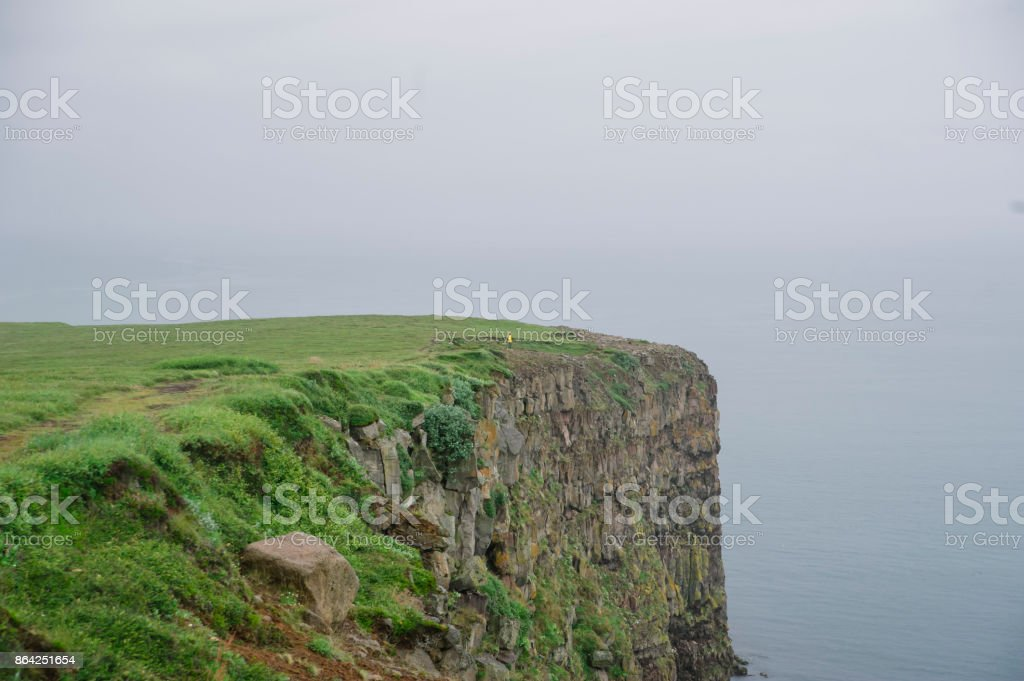 rock beach cliff edge on a foggy rainy weather, dark ocean royalty-free stock photo