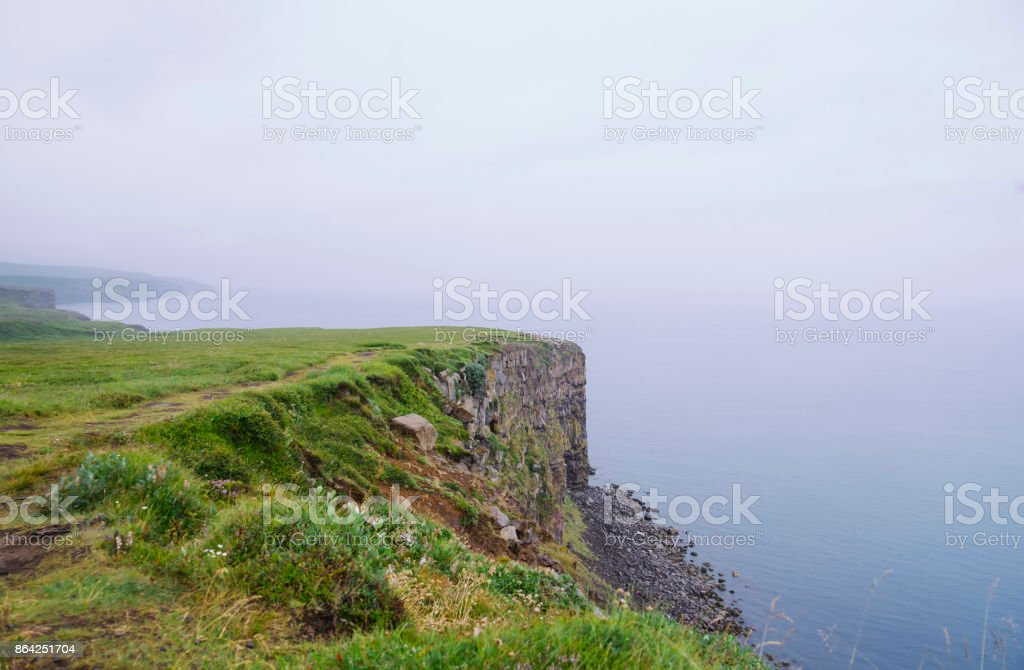 rock beach cliff edge on a foggy rainy weather, dark ocean royalty-free stock photo